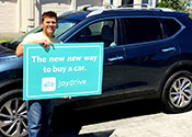 "A man standing at home in front of a new car holding a sign that says             ""The new new way to buy a car"""