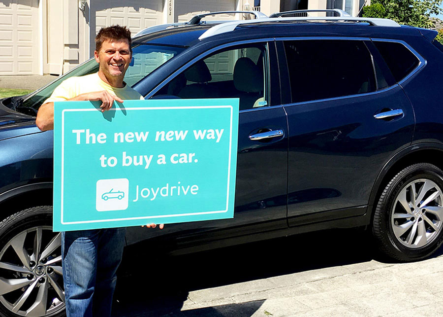 "A man standing at home in front of a new car holding a sign that says ""Joydrive #boughtonline"""