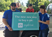 "A mother, father, and young sons standing in front of a new car holding a sign that says             ""The new new way to buy a car"""