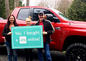"A mother, a father, and a daughter standing in front of a new car holding a sign above her head that says             ""Yes, I bought a car online"""
