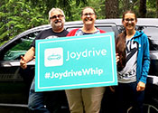 "A woman and a man standing in front of a new car holding a sign above her head that says             ""Joydrive #joydrivewhip"""