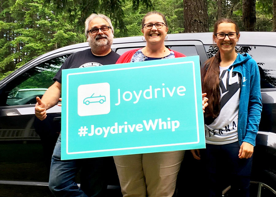 "A woman and a man standing in front of a new car holding a sign above her head that says ""Joydrive #boughtonline"""