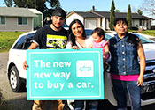 "A family standing in front of their home andj a new car holding a sign that says             ""The new new way to buy a car"""