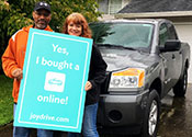 "A couple standing in front their home and a new car holding a sign above her head that says             ""The new new way to buy a car"""